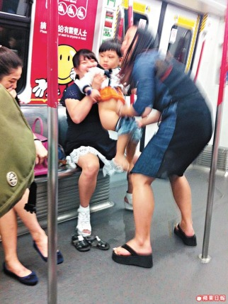 Two Mainland Chinese women is helping a toddler to pee on the floor inside a Hong Kong subway compartment.