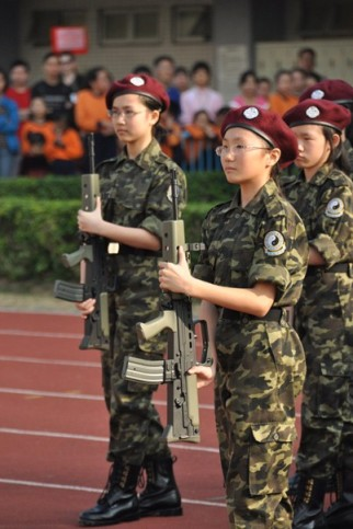 The little pioneers of Hong Kong national education are wearing uniforms with Yin-Yang emblems and holding L85 rifles.