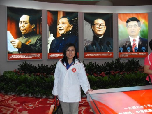 Hong Kong Pro-National Education Teacher Standing in front of Pictures of Chinese Leaders.