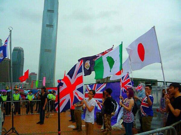 Protesters waive the Union Jack, British Hong Kong flag, Taiwan Independence flag, and Japanese flag in front of PLA camp.
